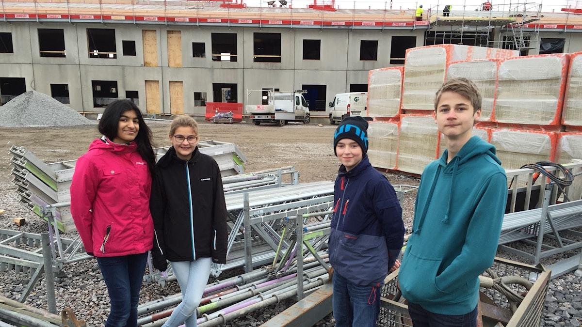 Eleverna i Älmhult står framför skolan som håller på att byggas upp.