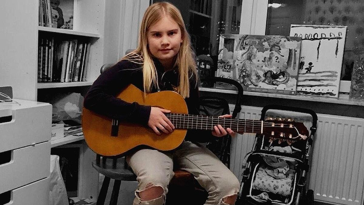 Elina istuu kitara sylissä