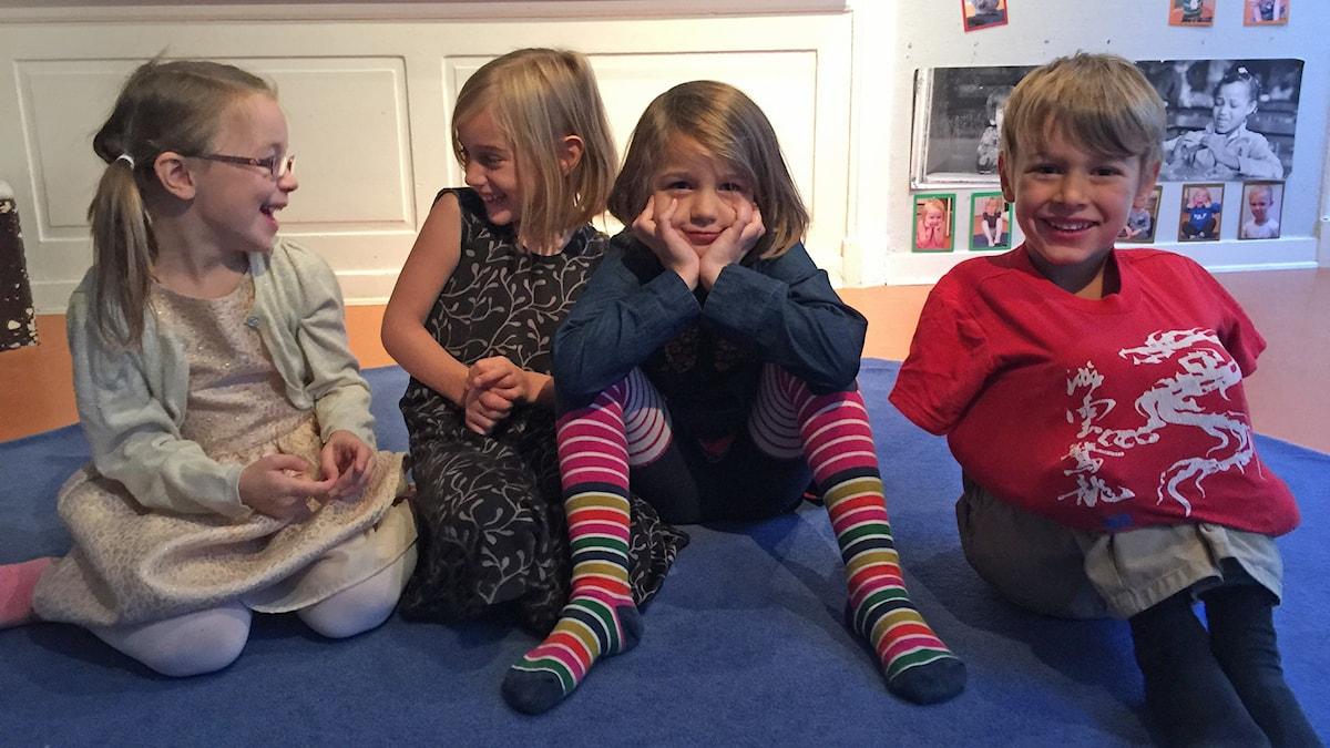 Kuvassa istuvat lattialla Emilia, Iris, Aili ja Benjamin.