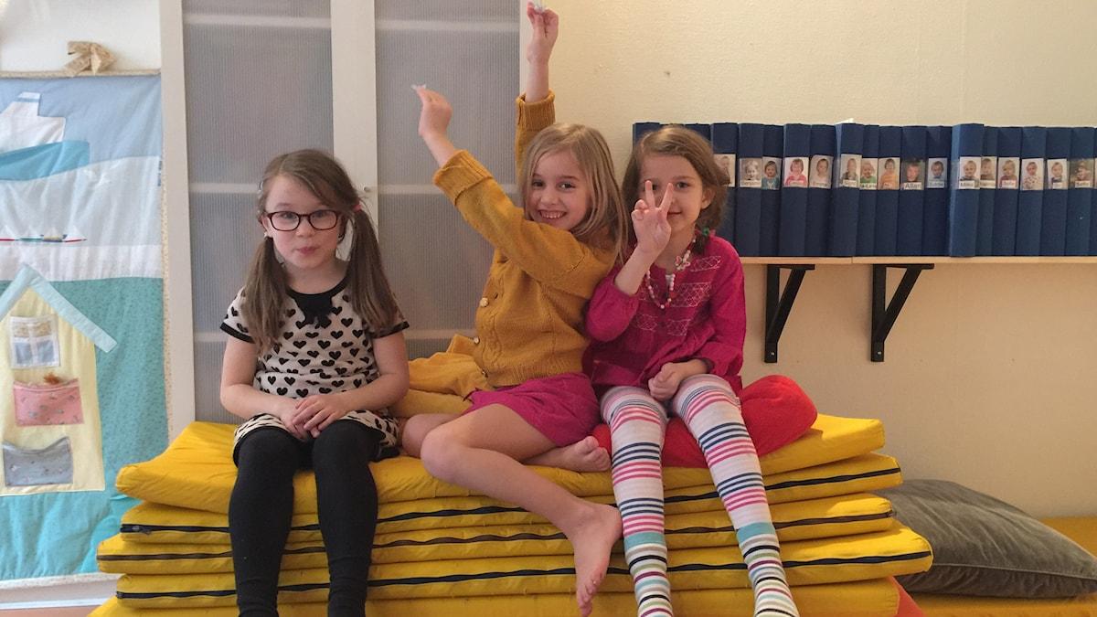 Kuvassa istuvat patjojen päällä Emilia, Iris ja Aili.