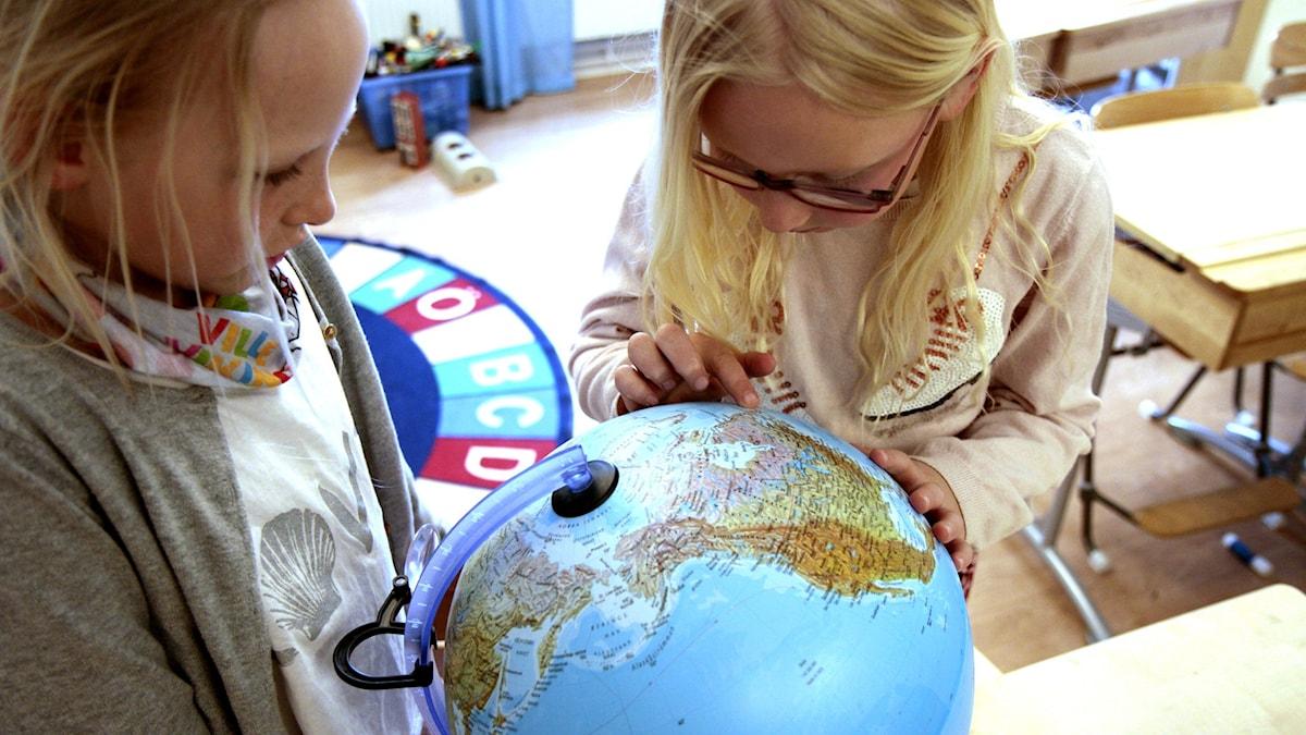 Isabella ja Signe tutkivat karttapalloa.