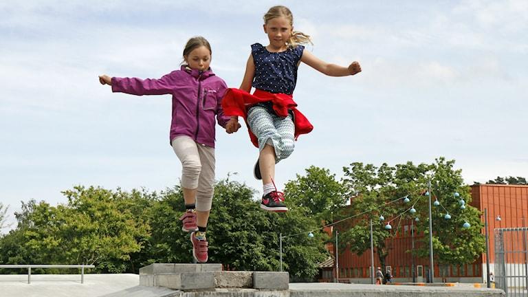 Kuvassa Laura ja Elina Janhunen hyppäävät ilmaan.