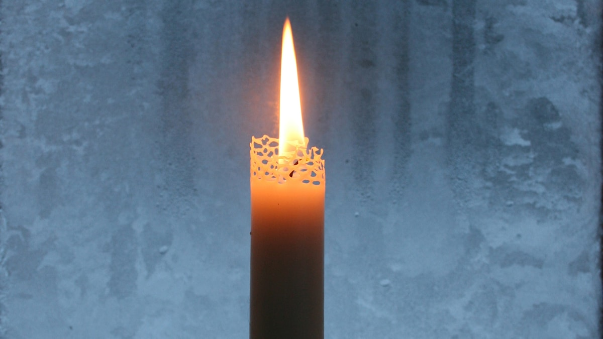 Kynttilä huurteisen ikkunaruudun vieressä
