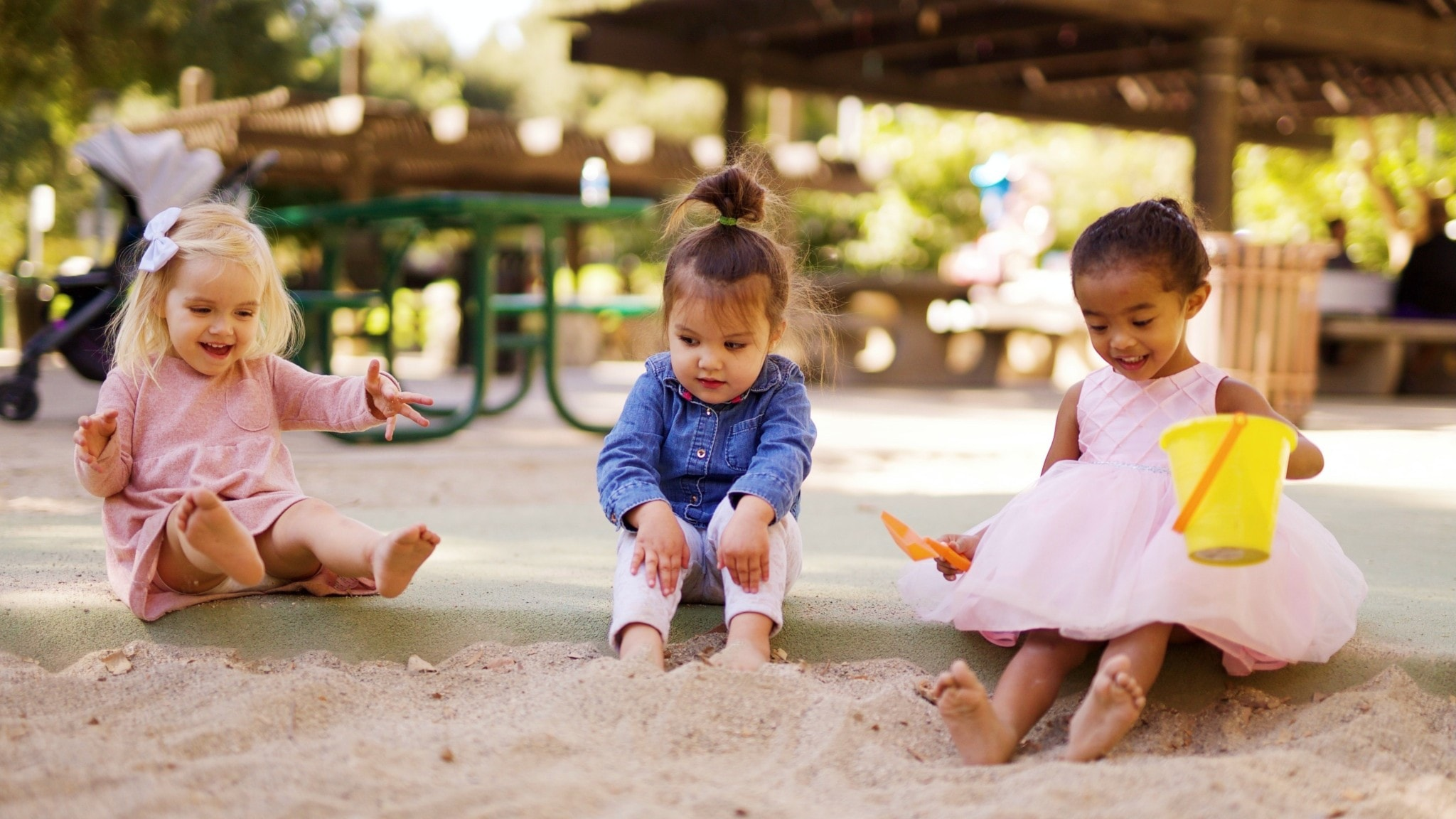 Kolme lasta leikkivät hiekkalaatikossa