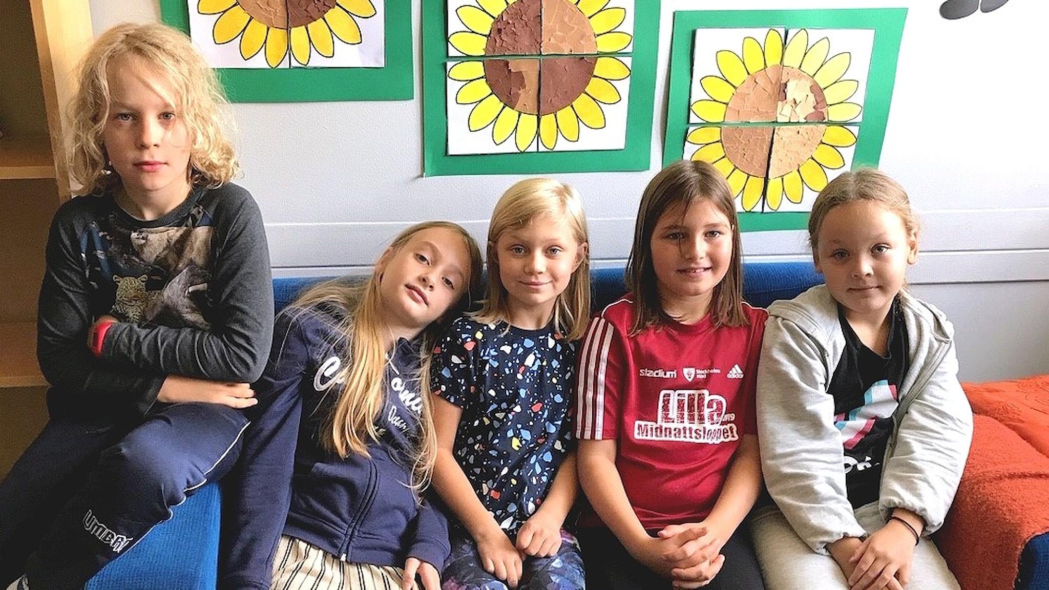 Viisi lasta istuvat rivissä sohvalla