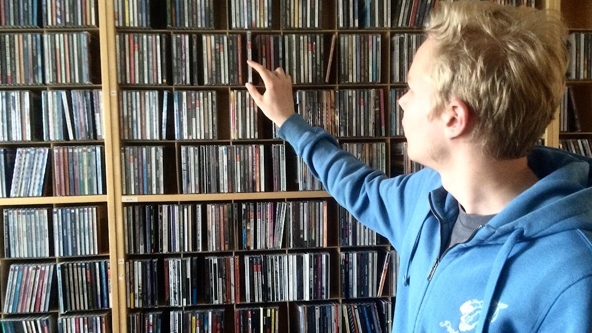 Joel Tekoniemi poimii levyjä hyllystä.