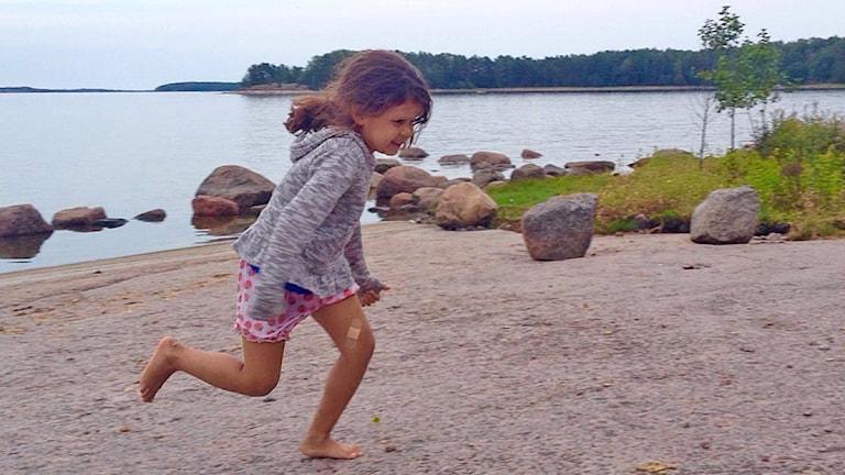 5-vuotias Aina juoksee rannalla.