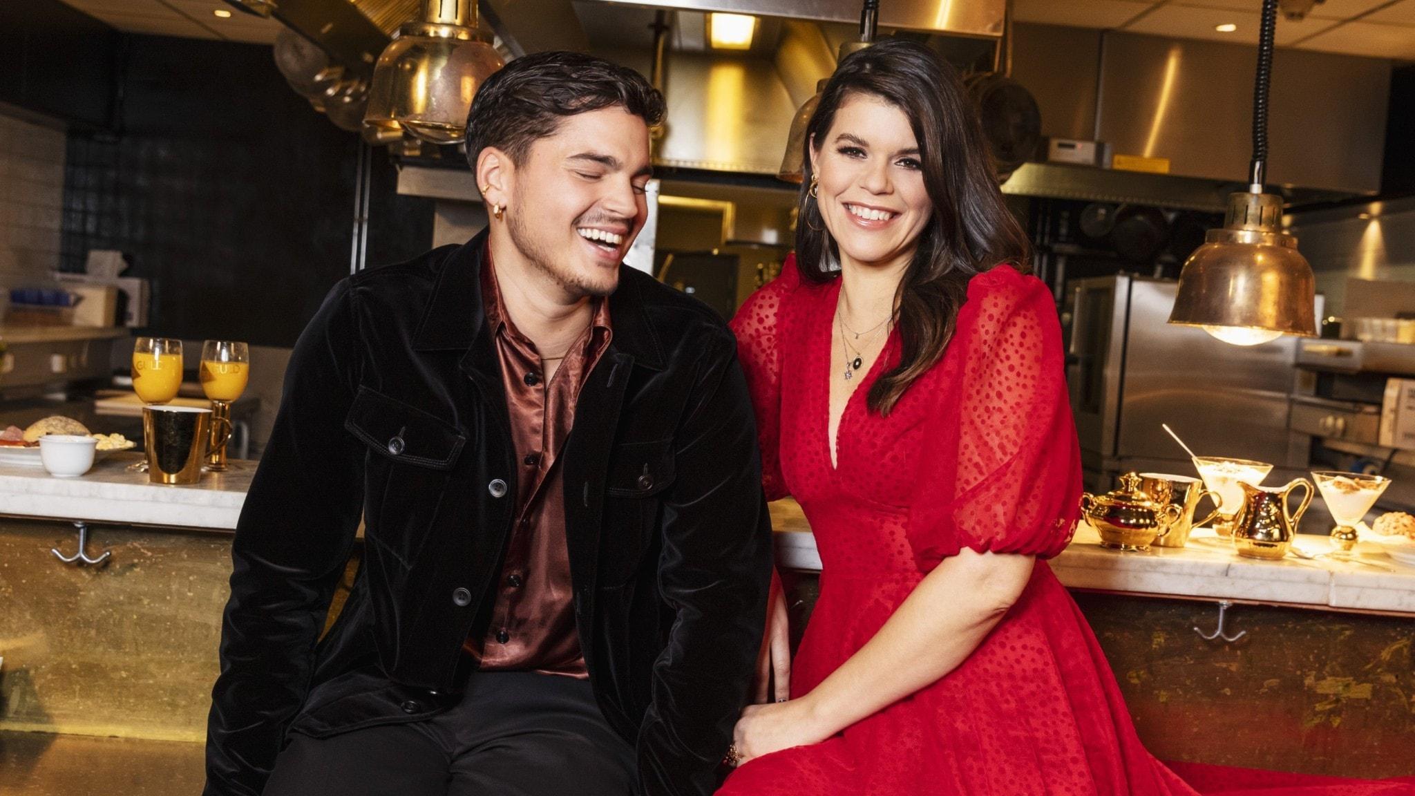 Programledarna Oscar Zia och Emma Molin sitter på en bänk och skrattar.