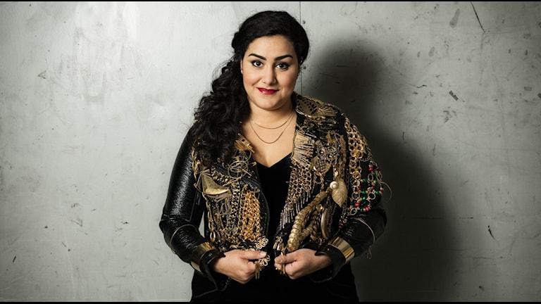 Tina Mehrafzoon står i guldig jacka, hon leder P3 Guld-galan