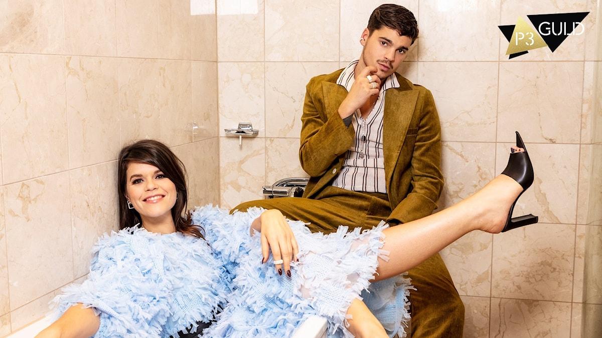 Programledarna Emma Molin och Oscar Zia i ett badkat.
