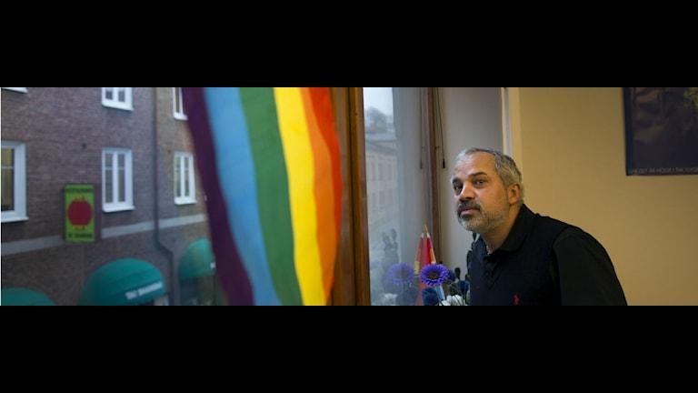 Ardeshir Bibakabadi framför en regnbågsflagga. Foto:Björn Larsson Rosvall/ Scanpix