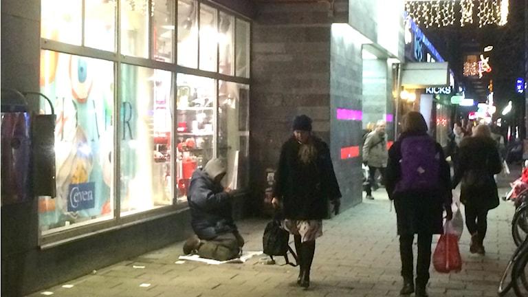 En tiggande man knäböjer framför ett skyltfönster i centrala Stockholm. Människor går förbi. Foto: Jenny Hallberg/Sveriges Radio.