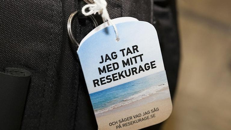 Adresslapp till resväska där det står: jag tar med mitt resekurage. Foto: Johan Jeppsson.