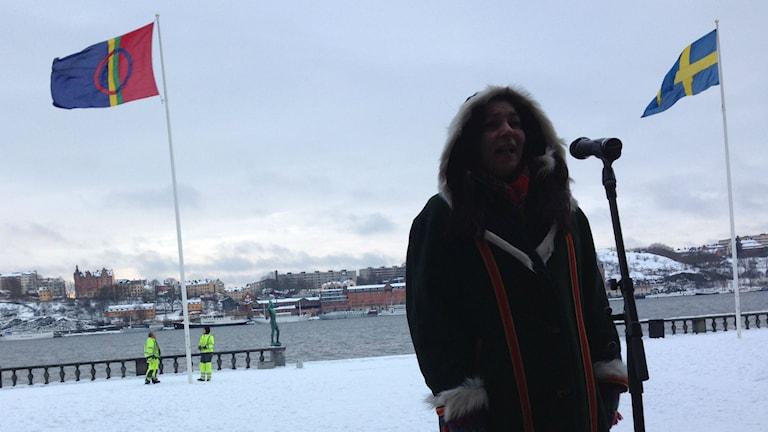 Cariola Rosdotter firar med jojk framför den samiska och svenska flaggan. Foto: Jörgen Heikki/Sveriges Radio