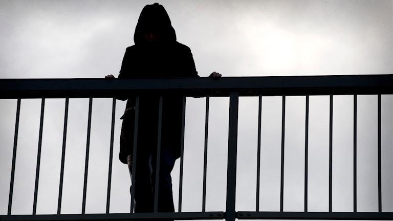 En kvinna i skugga står på en bro. Foto: Claudio Breschiani/TT.