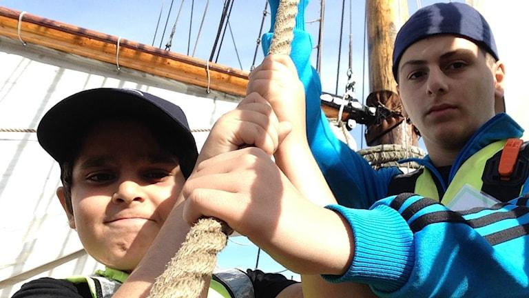 Elvaåringarna Allan och Josef hissar segel på segelfartyget Shamrock. Foto: Filip Jakobsson/Sveriges Radio.