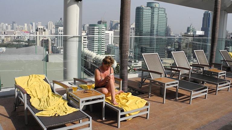 Kvinna i bikini solstol på en terass högt upp med utsikt över Bangkok. Foto: Leif R Jansson/TT.