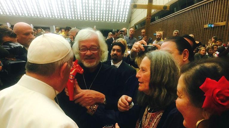 Svenska romer samlas kring påven, och en av dem räcker fram en dalahäst. Foto: privat.