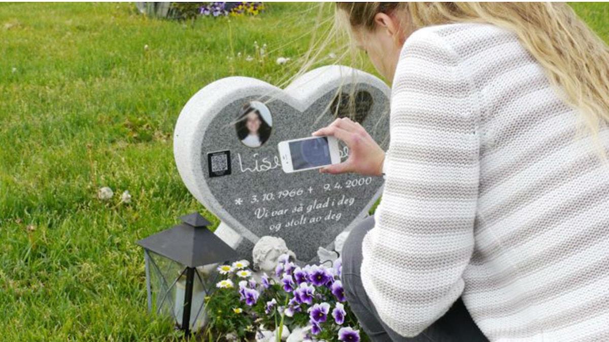 En tjej på en ung tjejs grav där hon med sin mobil avläser QR-koden från gravstenen. Foto: Sveriges begravningsbyråers förbund (SBF)