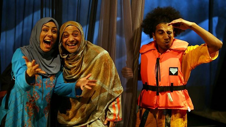 Två personer skrattar och tittar ut mot publiken. Den tredje, i klädd flytväst, kisar och spanar ut. Foto: Strobemedia.