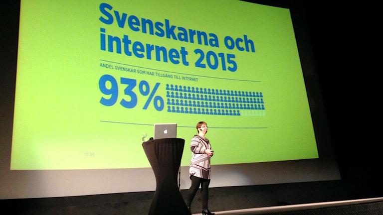"""Pamela Davidsson, statistikchef på Internetstiftelsen i Sverige står på en scen och presenterar rapporten """"Svenskarna och internet 2015"""". Foto: Ingrid Forsberg/Sveriges Radio."""