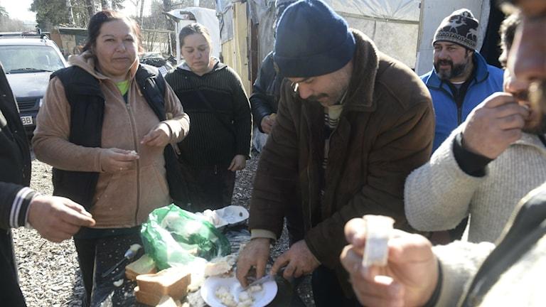 Romer boendes i ett läger i Sollentuna äter.
