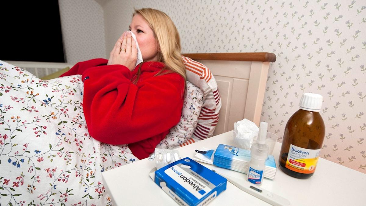 En förkyld kvinna ligger i en säng och snyter sig. På nattduksbordet är det fullt med mediciner. Foto: Jonas Ekströmer/TT.