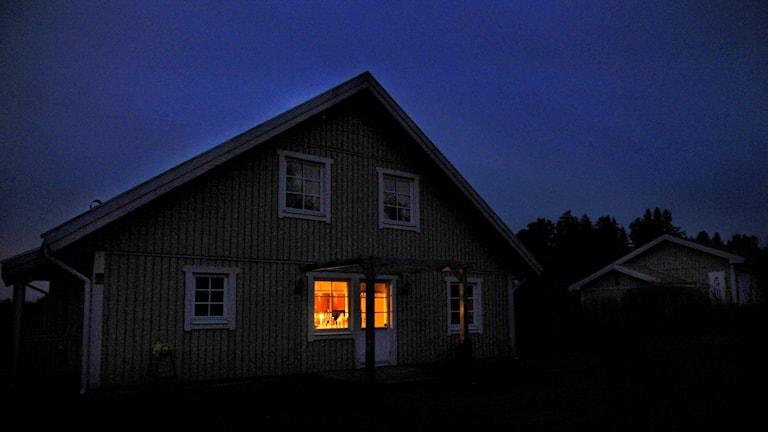 Nattbild på ett hus där det lyser av stearinljus i ett av fönstren. Foto: Tomas Oneborg/TT.