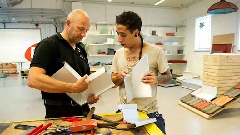 Yrkesutbildning är ett sätt att lösa ungdomsarbetslösheten. På bilden står en gymnasielärare tillsammans med en elev som läser plåtslagarutbildningen i Katrineholm. De håller i varsin bit plåt och diskuterar något. Foto: Fredrik Sandberg/TT