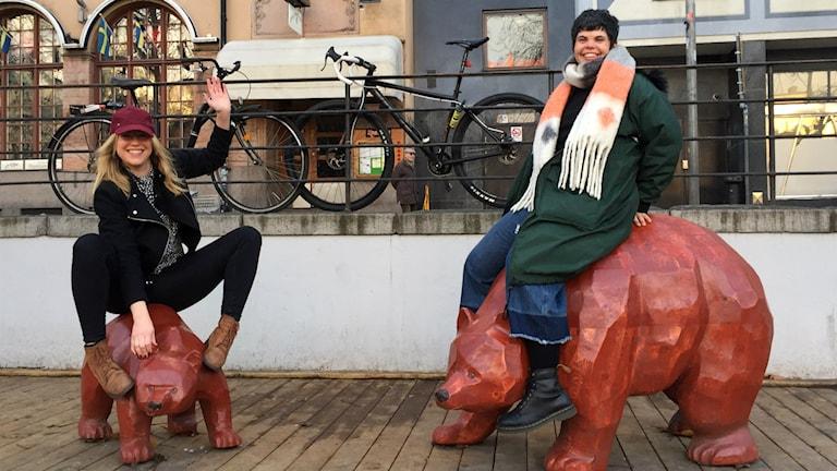 Linda Karlsson och Sannah Salameh sitter på varsin björnstaty utomhus i Björns trädgård i Stockholm. Foto: Isabelle Swahn/Sveriges Radio.