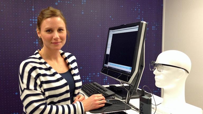Cecilia Eriksson på teknikföretaget Tobii står framför en dator för att visa hur företagets ögonstyrningsteknik fungerar. Hon har på sig en randig kofta och har rödlätt hår. Foto: Isabelle Swahn/Sveriges Radio.
