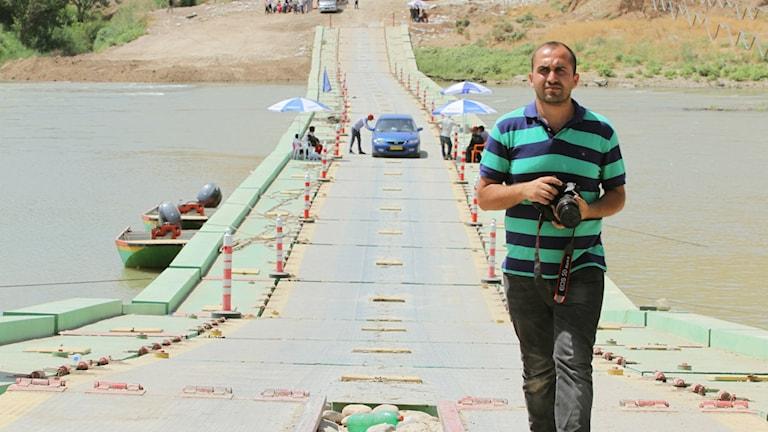 En man går på en bro. I handen håller han en kamera. Bakom står en bil och människor. Foto: Hogir Hirori.