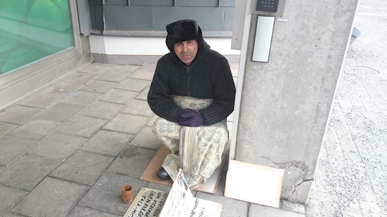 Shaban Ibram sitter och tigger utanför en kontorsbyggnad i Stockholm. Foto: Rafal Szoppe/Sveriges Radio.