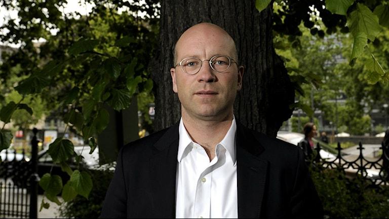 Man i kostym och glasögon tittar in i kameran, står framför ett träd.