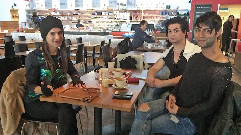 Tre personer sitter vid ett bord och fikar. Foto: Rafand Ahmad/Sveriges Radio.