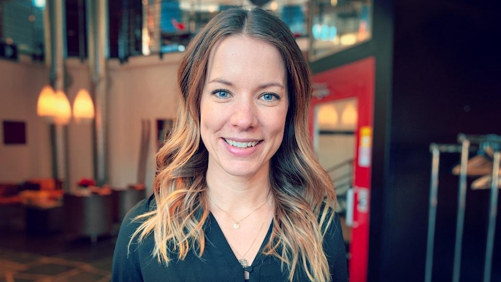 En leende kvinna i brunt hår står i i ett öppet rum med tre gula taklampor bakom sig.