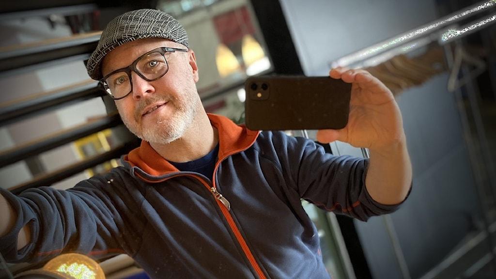 En man i glasögon fotar sig med en mobiltelefon i en spegel.