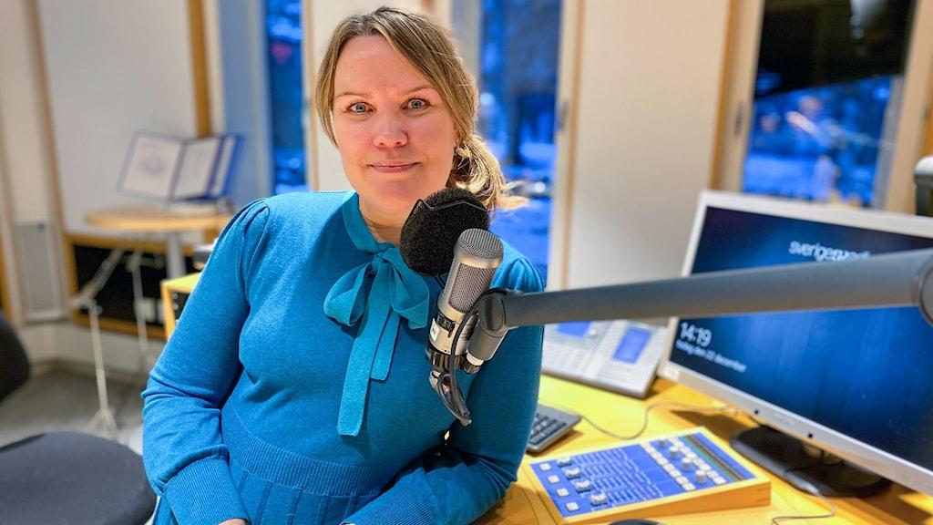En kvinna med blond hår står i en radiostudio lutat mot bordet och en mikrofon mot ansiktet.