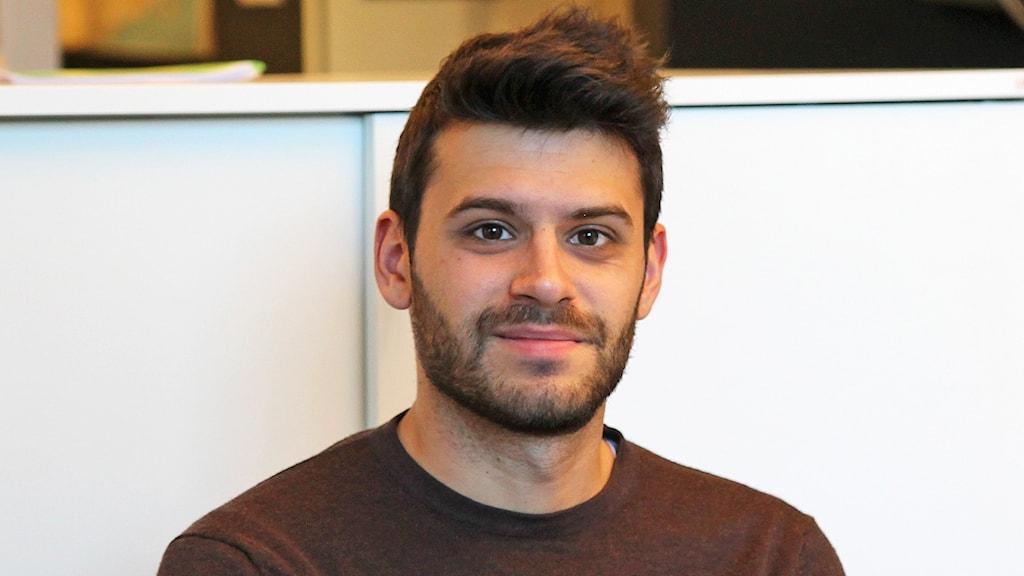 Ung man med brunt kortklippt hår och brun tröja framför vitt skåp