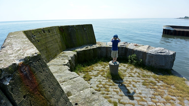 En pojke blickar ut över havet på Sveriges sydligaste udde Smygehuk