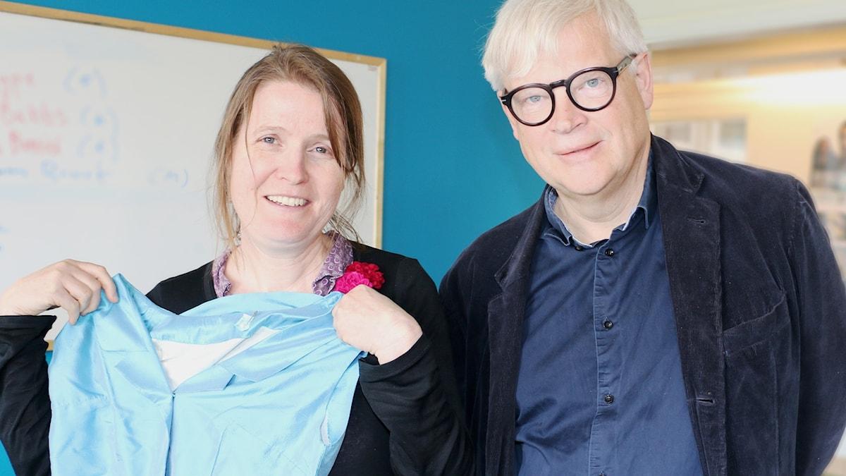 Louise Epstein & Thomas Nordegren. Louise håller upp en blå klänning och Thomas är klädd i en blå skjorta och en blå kavaj.