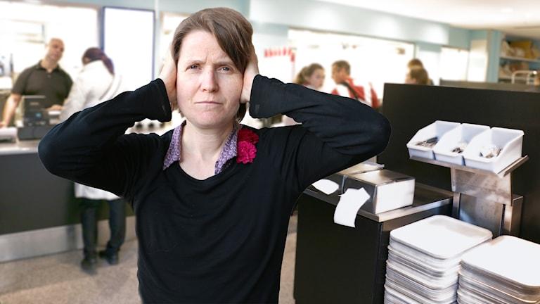Louise Epstein håller sig för öronen och tittar bistert in i kameran. I bakgrunden syns kön till en lunchbespisning.