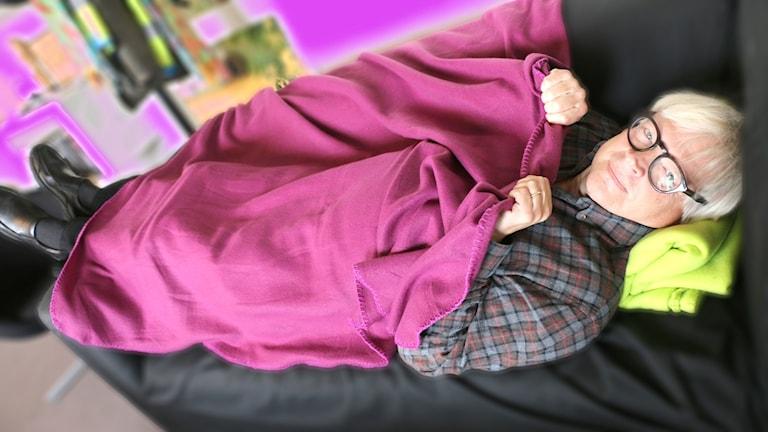 Thomas Nordegren ligger med en lila filt över sig på en soffa för att illustrera sin egen begravning.