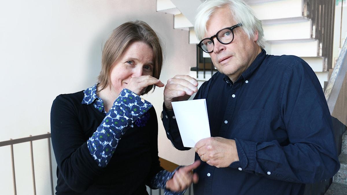 Louise Epstein och Thomas Nordegren illustrerar ett valögonblick genom att huka och se rädda ut bakom en papperslapp.
