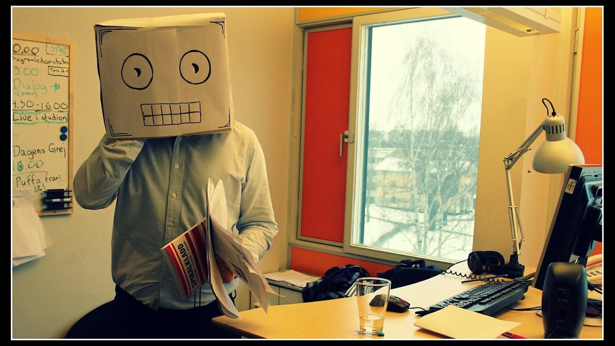 Henrik Torehammar med en kartong på huvudet föreställande ett robothuvud. Foto: Ronnie Ritterland / Sveriges Radio Robothuvudet är skapat av Ronnie Ritterland och tecknat av Jennifer Kucukaslan.