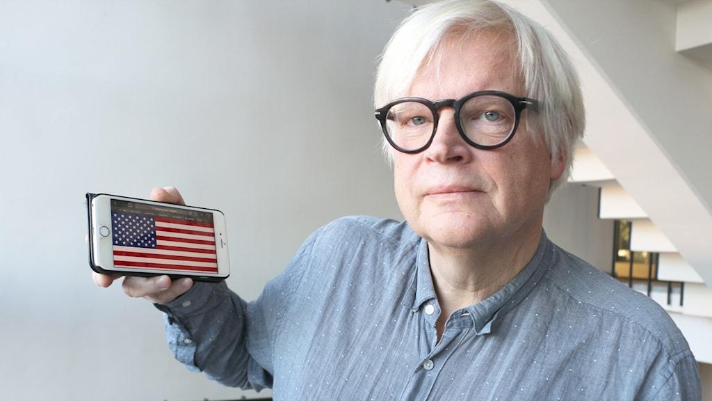 Thomas Nordegren håller i en iphone som visar amerikanska flaggan på skärmen.