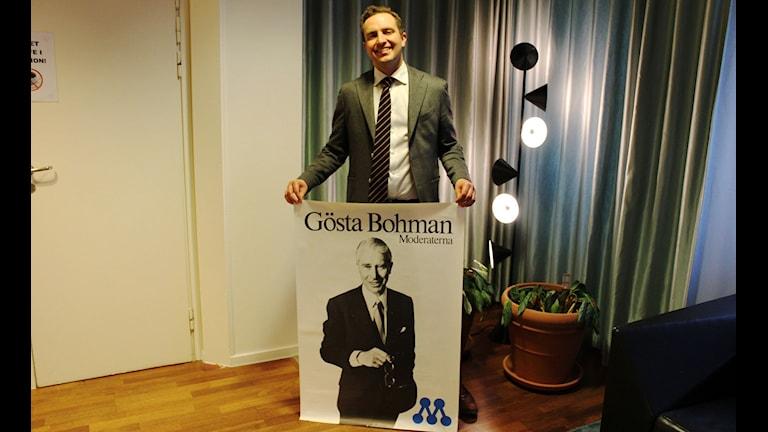 Moderaternas partisekreterare Tomas Tobé med en Gösta Bohman-affisch, partiets bidrag till Nordegrens & Epsteins politiska museum. FOTO: Cecilia Djurberg/Sveriges Radio