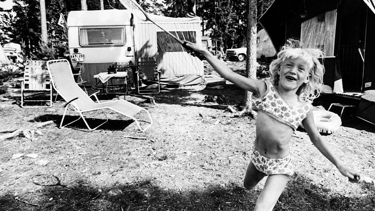 En svartvit bild som illustrerar sommarlov - en glad flicka springer fram med ett badmintonracket i ena handen i campingmiljö.