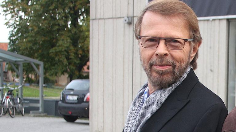 Björn Ulvaeus ler mot kameran utanför Radiohuset i Stockholm.
