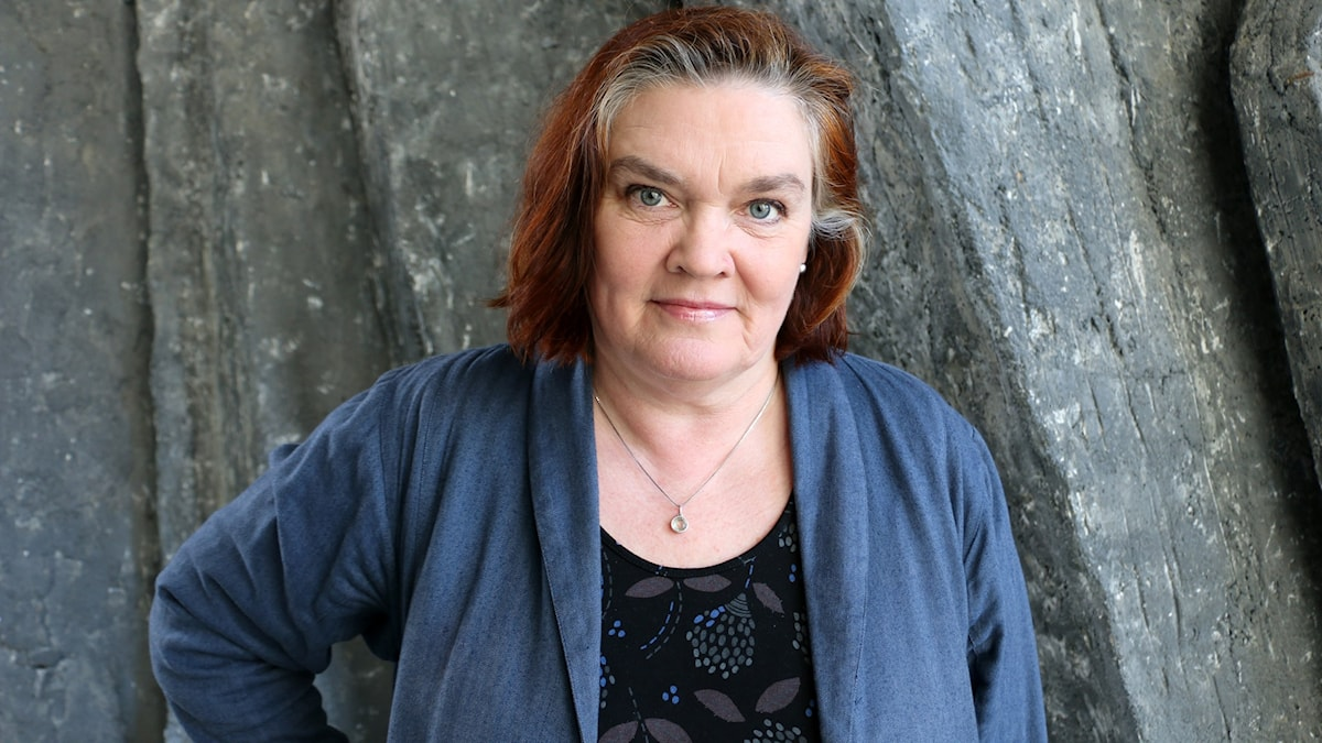 Maja Hagerman, författare medverkar i Nordegren & Epstein i P1. På bilden står Maja med en arm i sidan och tittar med skarp blick rakt in i kameran.